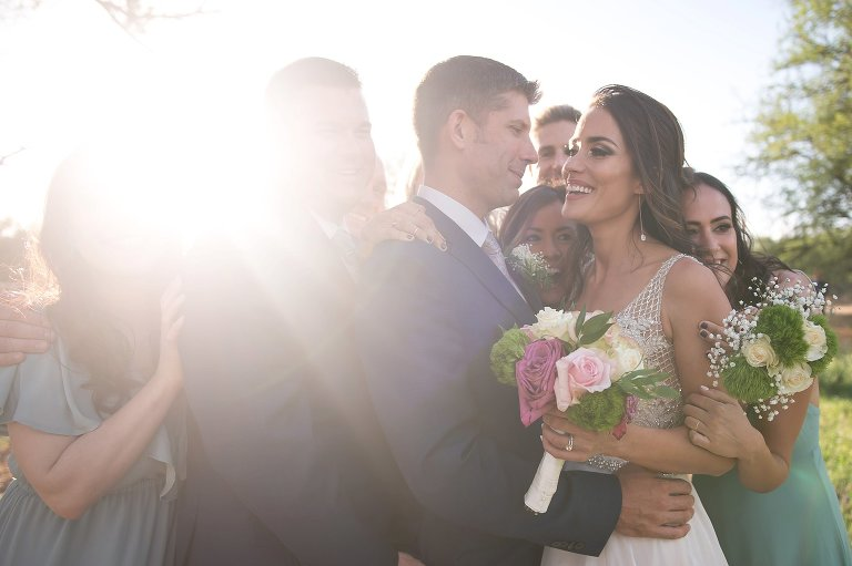 Bridal party hugging bride and groom after ceremony with lens flare